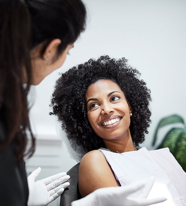woman in dental chair speaking with her dentist