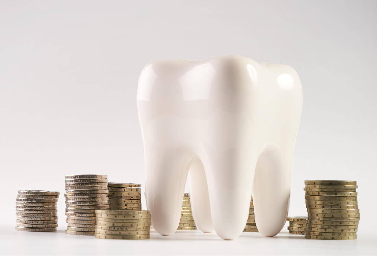 A tooth surrounded by piles of coins to represent dental insurance