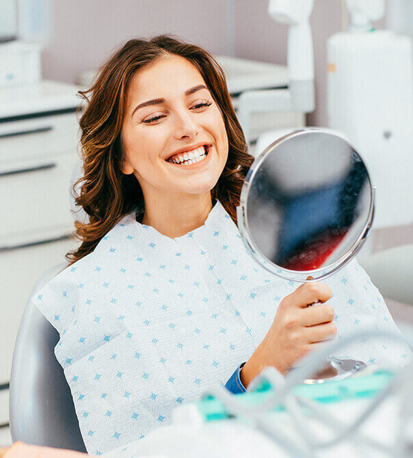 woman looking at her white smile in a mirror