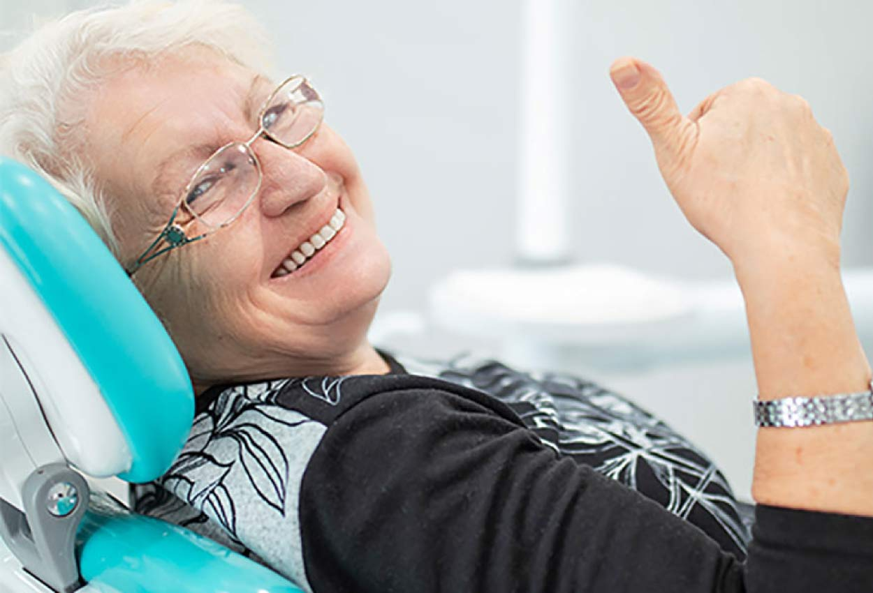 senior woman smiles and gives up thumbs up in the dental chair