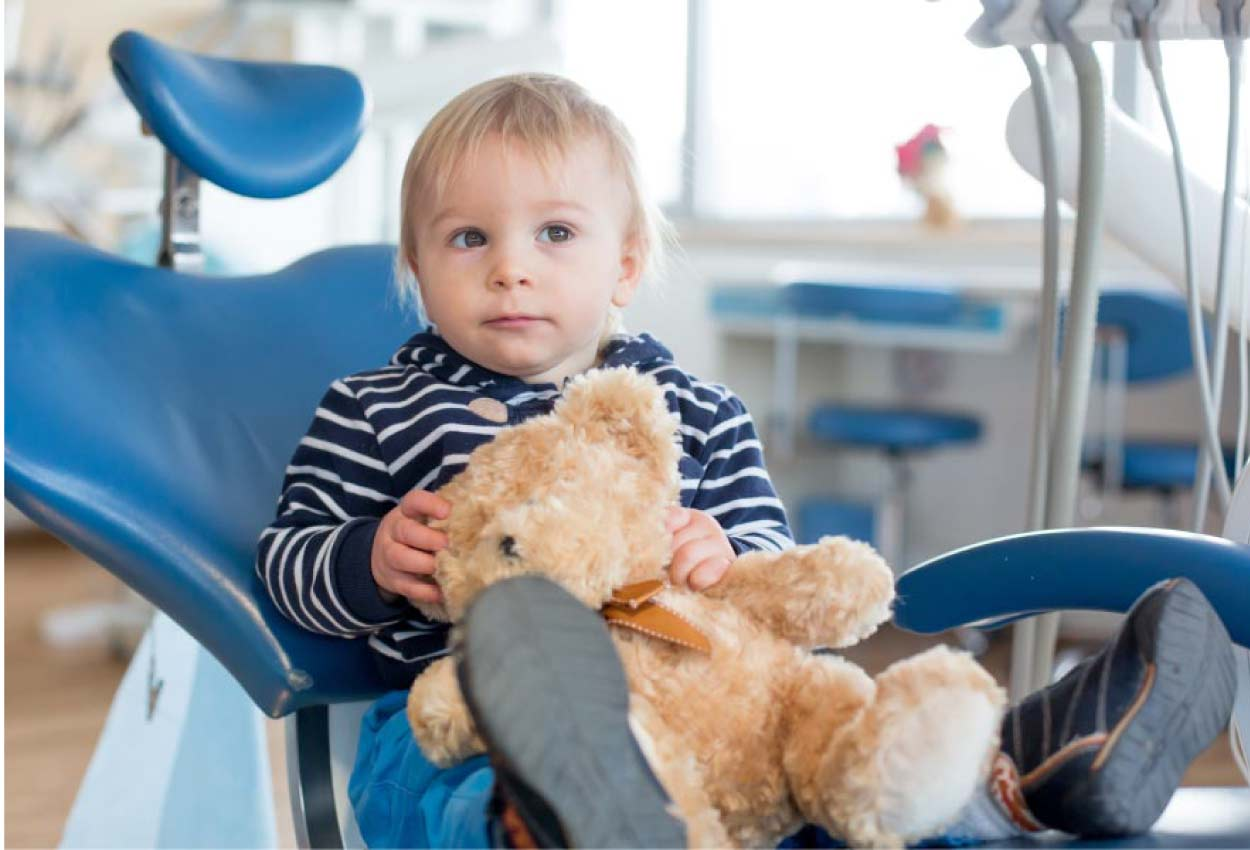 young boy holding a teddy bear in the dental chair