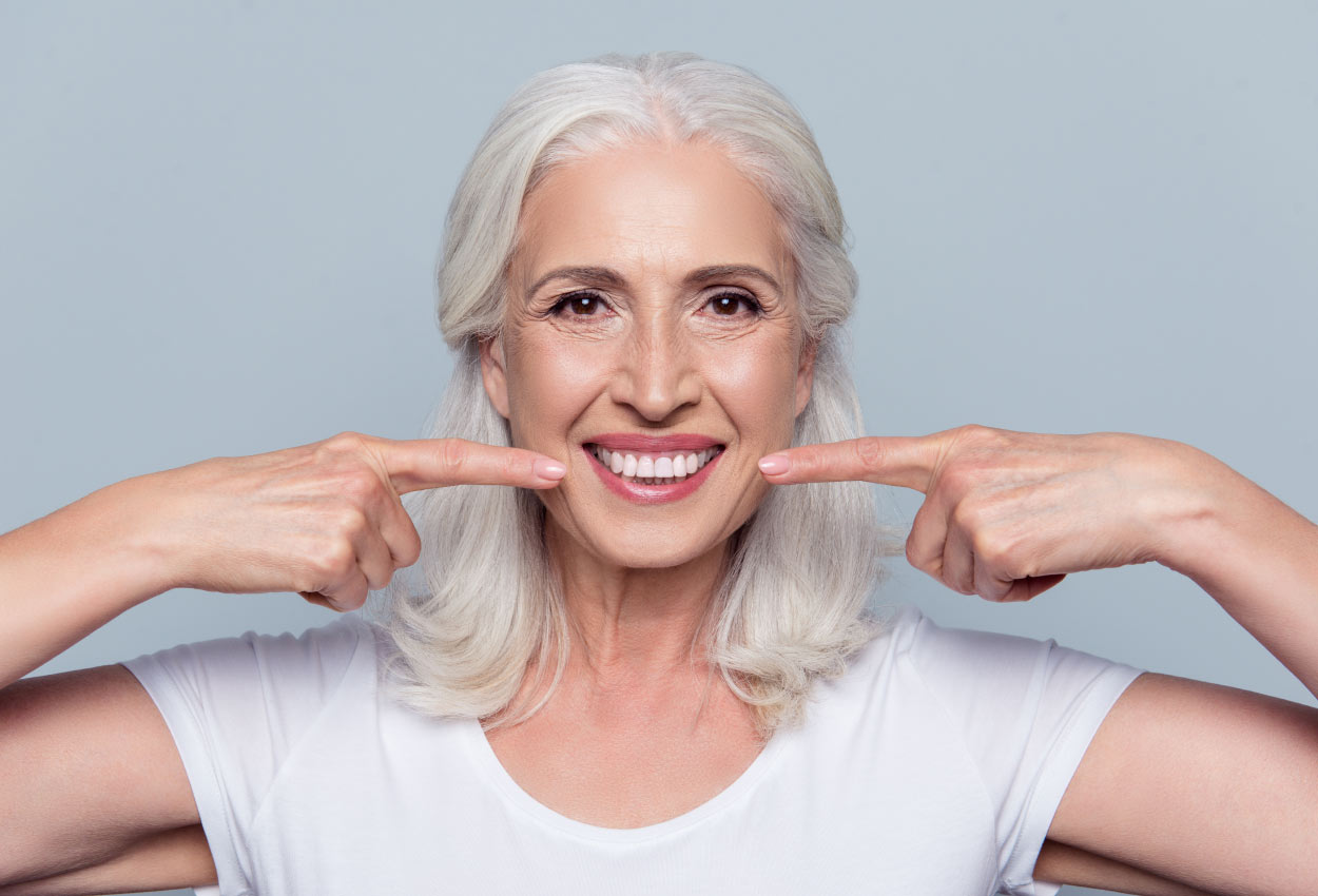white-haired woman points at her teeth after a full smile restoration in Arlington, VA