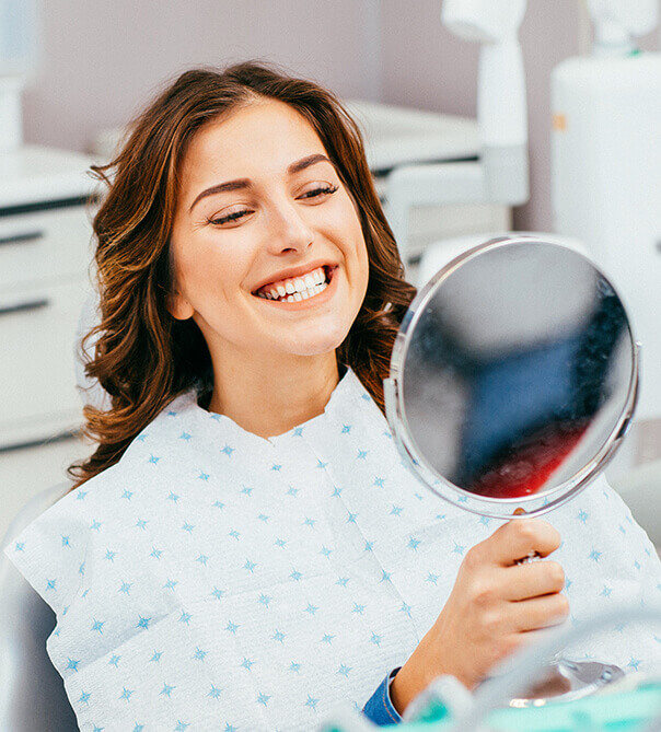 woman examining her smile in mirror