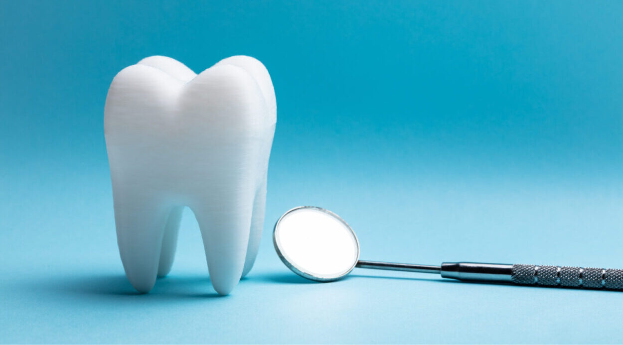 Closeup of a white tooth next to a special dental mirror used at the dentist