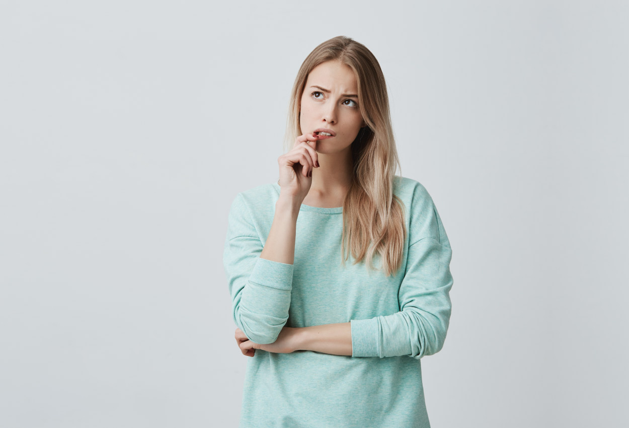 Blonde woman in a turquoise shirt wonders if teeth whitening will make her teeth sensitive